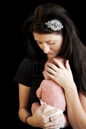 Proud mother cuddles her newborn baby