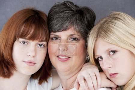 Image of smiling caucasian mother and her two daughters