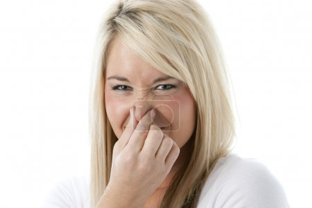 Caucasian young adult woman holding her nose as if she smells something bad