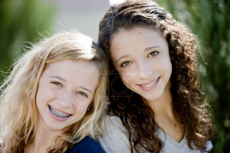 Two smiling caucasian teenage girls in the park