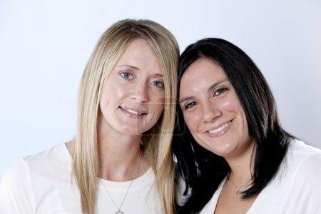 Photo pour Bleu d'éclairage spécial obtenir effet. un headshot de deux souriant amis caucasien femmes adultes real. - image libre de droit