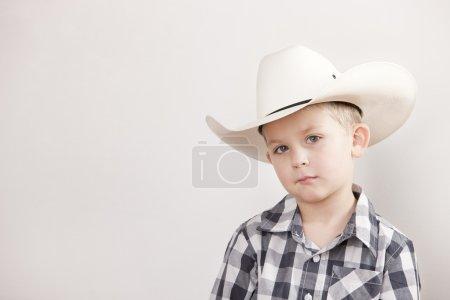 Serious little boy wearing a cowboy hat