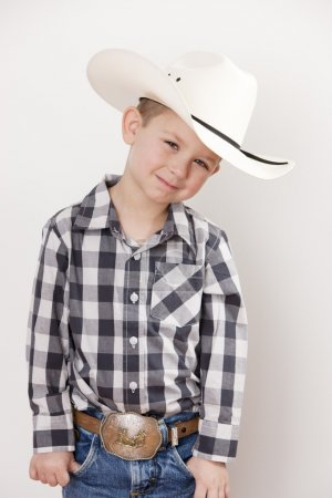 Waist up image of smiling little boy in cowboy hat, plaid shirt and a big belt buckle