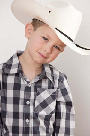 Smiling little boy in cowboy hat, plaid shirt and a big belt buckle