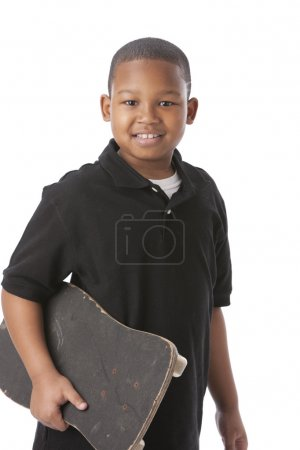 Photo for A waist up image of an 8 year old african american little boy holding his skateboard - Royalty Free Image