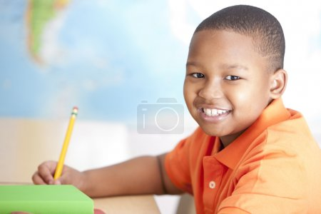 Image of african american little boy studying in school