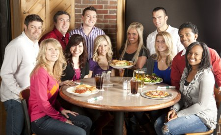 Waist up image of eleven adults at a restaurant