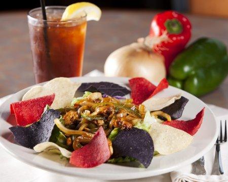 Photo pour Une salade de fajita avec des chips de tortilla croustillantes et un verre de thé glacé rafraîchissant . - image libre de droit