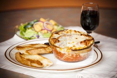 Photo pour Un bol de lasagnes cuites au four avec du pain à l'ail avec une salade latérale et un verre de vin rouge . - image libre de droit