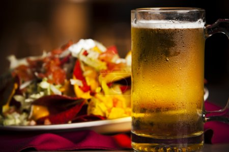 Food and Drink. A closeup image of spicy nachos with a cold, frosty mug of beer.