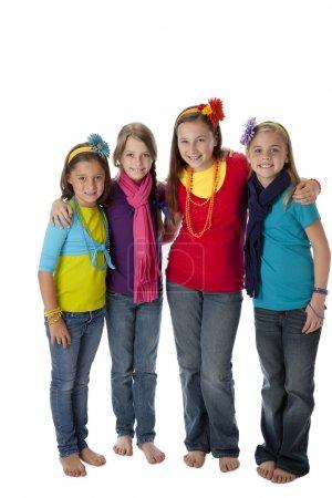 Photo pour Une image pleine longueur d'un groupe de quatre petites filles diverses avec leurs bras autour de l'autre pour l'amitié . - image libre de droit