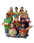 Zdravé stravování. Skupina dětí, které drží košíky s řadou zdravých potravin