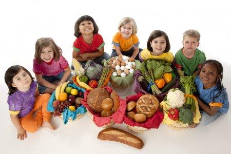 Foto de Una imagen de alto ángulo de un grupo diverso de niños sosteniendo canastas con los grupos de alimentos de frutas, verduras, lácteos, carnes y granos. - Imagen libre de derechos