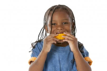 Healthy Eating. Black little boy making a happy face with an orange in his mouth