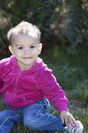 Real : Smiling mixed race little girl sitting happily in a sunny park