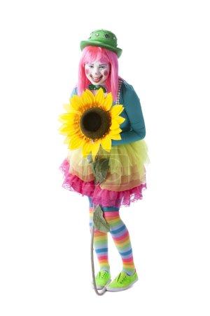 Photo pour Une image pleine longueur d'une jeune adolescente clown agissant comme un mime tenant une grande fleur . - image libre de droit