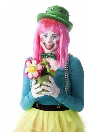 Photo pour Une image de taille d'une adolescente clown tenant un pot de fleurs . - image libre de droit