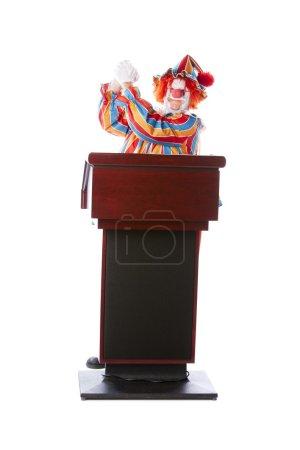 Photo pour Une image complète d'un clown adulte debout sur un podium prononçant un discours avec des gestes de main comme candidat politique gagnant . - image libre de droit