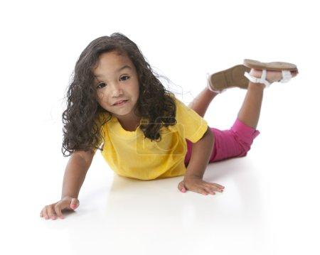 Photo pour Une image pleine longueur d'une race mixte souriante, noire et caucasienne, petite fille portant du jaune. Elle est allongée par terre. . - image libre de droit