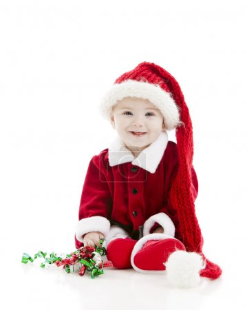 Little baby boy dressed as santa claus plays with christmas ribbon.