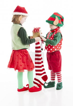 Two little Christmas elves put gifts in a christmas stocking for santa claus