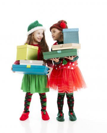Two little girl christmas elves carry tall stacks of wrapped presents