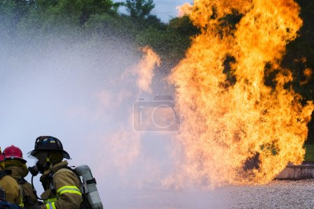 Photo for Firefighters work to extinguish a blaze.Firefighters foreground, water spray middle ground, flames in background. Notice the natural distortion from the water spray, and heat waves from the flame. To retain file integrity, this file is unprocessed - Royalty Free Image