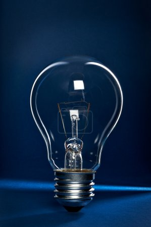 Photo for Light bulb on blue and black background - Royalty Free Image
