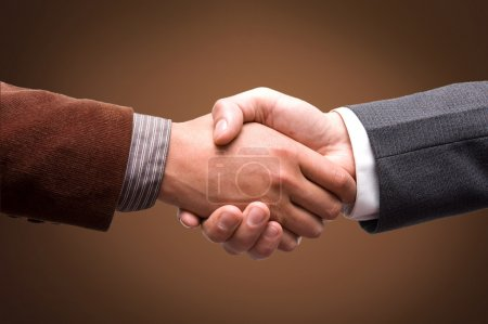 businessmen shaking hands on a black and brown background
