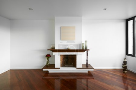Big empty living room with a chimney, white wall and wooden floo