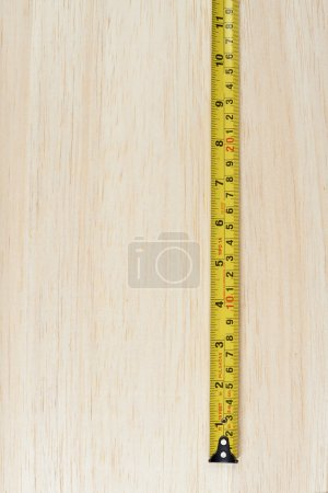 Tape measure over wooden background