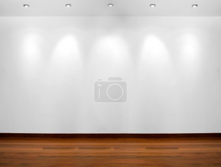 Empty white wall with 3 spot lights and wooden flo...