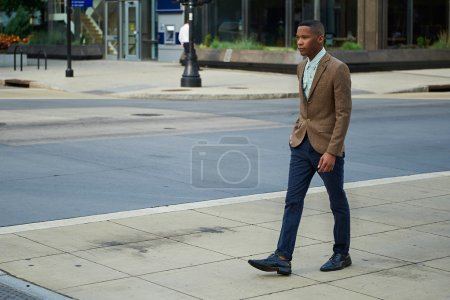 Young successful African - American business man walking in the