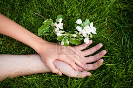 Photo for Hands of lovers on grass with flowers - Royalty Free Image