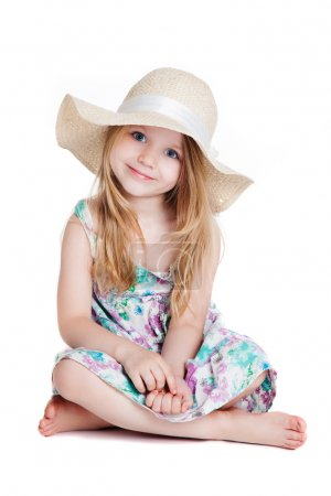 little blonde girl wearing hat and dress sitting on the floor