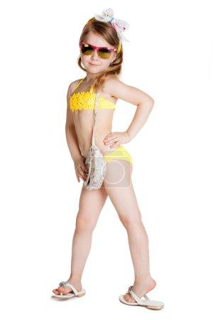 Foto de Niña rubia vistiendo traje de baño, gafas de sol y bolso sobre fondo blanco - Imagen libre de derechos
