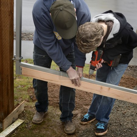 Father and Son Building a Gate