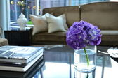 Coffee Table books, flowers and couch in hotel lobby