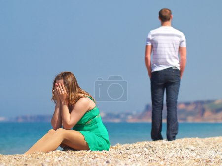 Photo for Couple had quarreled on the beach near the sea - Royalty Free Image