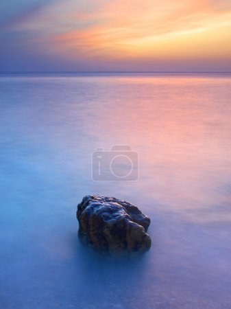 Photo pour Coucher de soleil sur la mer avec une couleur vive sur le ciel et la pierre sur le premier plan - image libre de droit