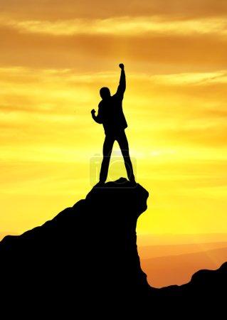 Photo pour Silhouette de champion sur le rocher. sport et vie active - image libre de droit