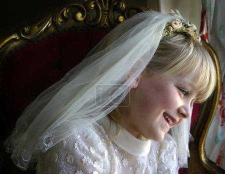 Photo pour Une jeune fille portant sa première robe de communion et son voile - image libre de droit