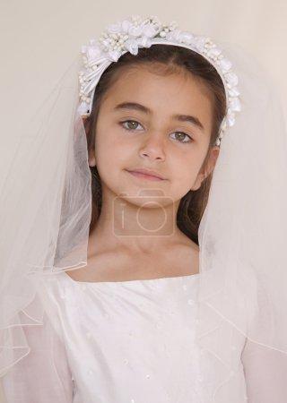 Photo pour Portrait d'une jeune fille au regard sérieux qui célèbre sa sainte communion. La fille regarde droit dans la caméra avec de grands beaux yeux . - image libre de droit