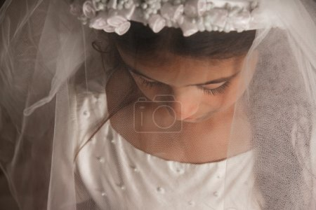 Photo pour Fille célébrant sa première communion. Son visage est couvert de son voile, et elle regarde vers le bas. Triste, sentiment sérieux. Photo horizontale - image libre de droit