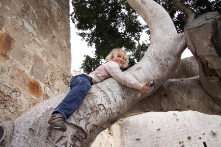 Mischievous girl climbing up a tree...