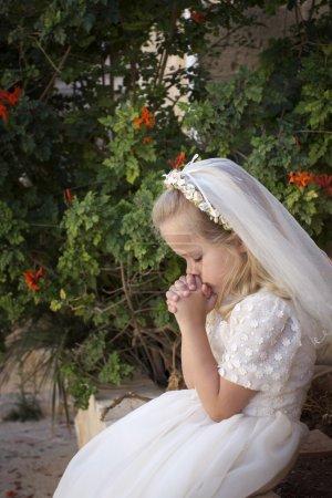 Photo pour Une jeune enfant priant pendant sa première communion - image libre de droit