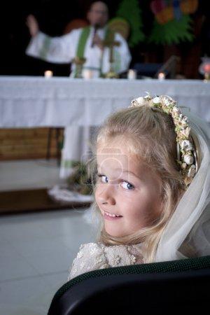 Photo pour Un jeune enfant faisant sa première communion catholique assiste à la messe avec un prêtre près de l'autel - image libre de droit