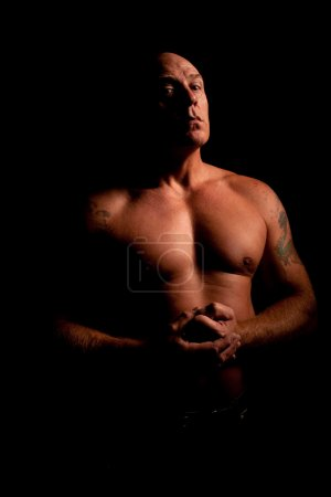 Low key portrait of muscular middle aged man