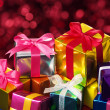 Постер, плакат: Pile of small gifts on red blurry lights background
