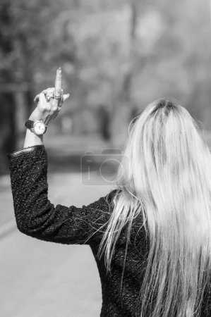 Photo for Young blonde woman walking away showing her middle finger. In black and white - Royalty Free Image